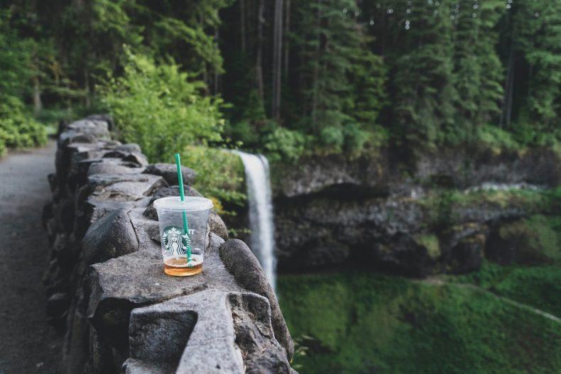 Copo de plástico em cima de um muro de pedra no meio da natureza com cascata em plano de fundo