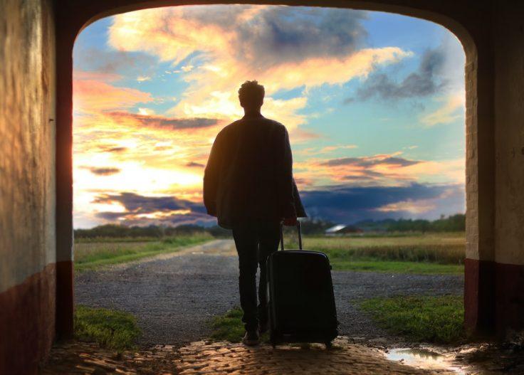 Silhueta de pessoa a transportar uma mala de viagem com paisagem natural de fundo