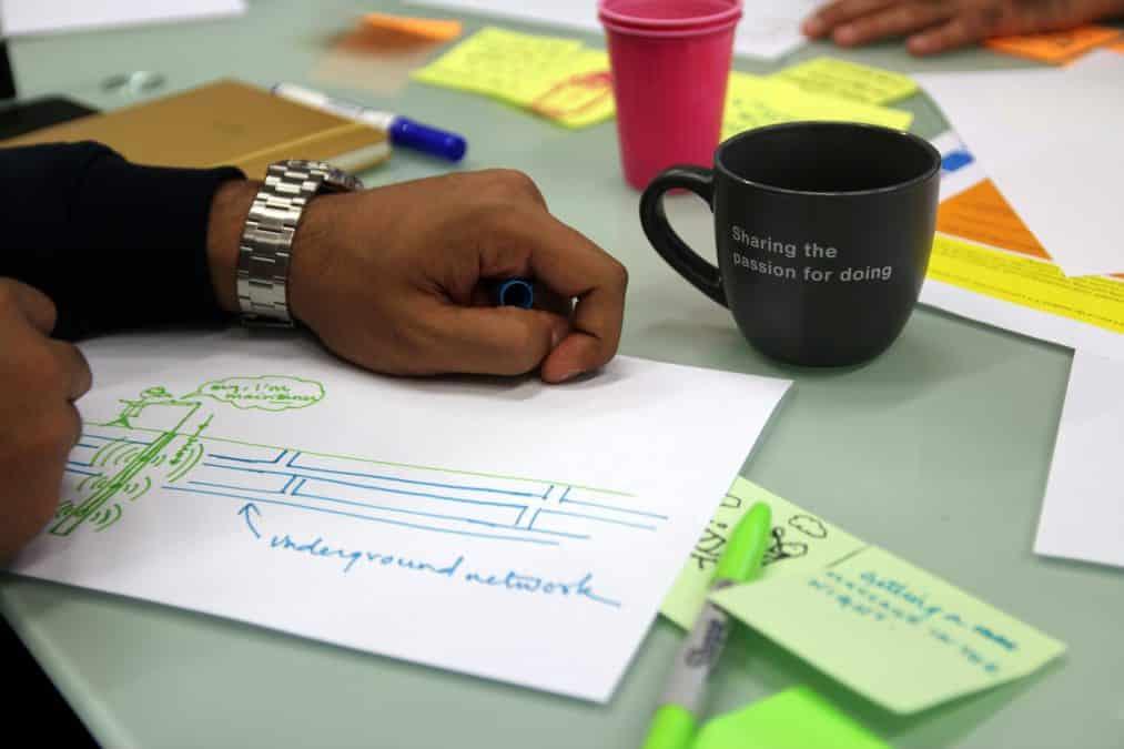 Mesa com um desenho, marcadores e uma caneca