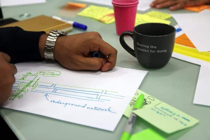 Pessoa a escrever numa folha com marcador com uma caneca e post-its ao lado