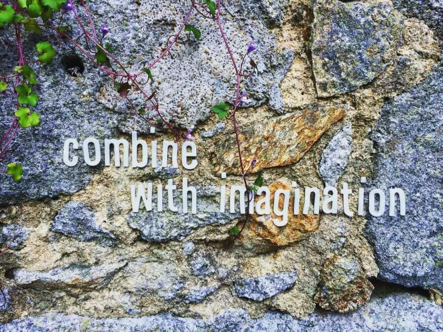 """Letras recortadas e coladas numa parede de pedra onde diz """"Combine with imagination"""""""