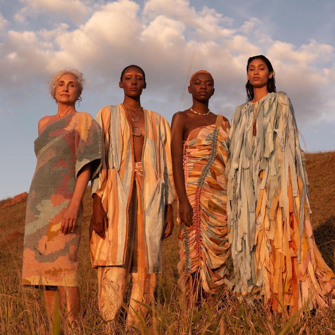 4 mulheres posam apara a foto no meio do campo