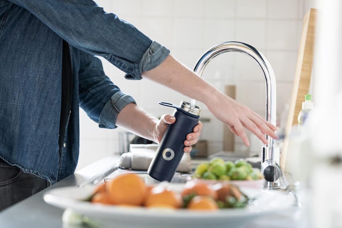 Pessoa a encher garrafa de água reutilizável
