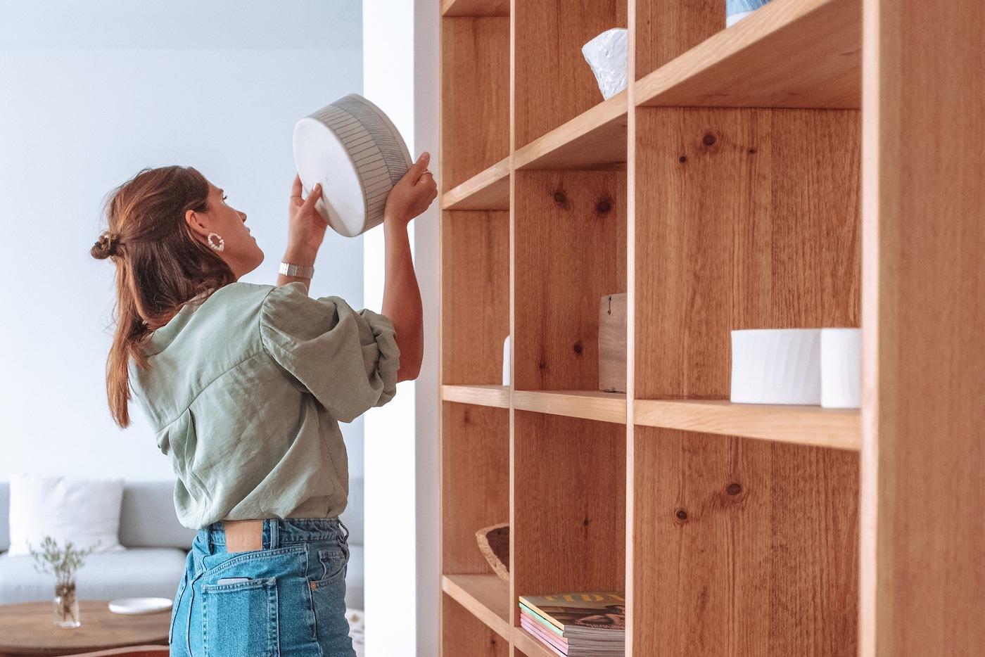 Joana a explorar estante com artigos de decoração