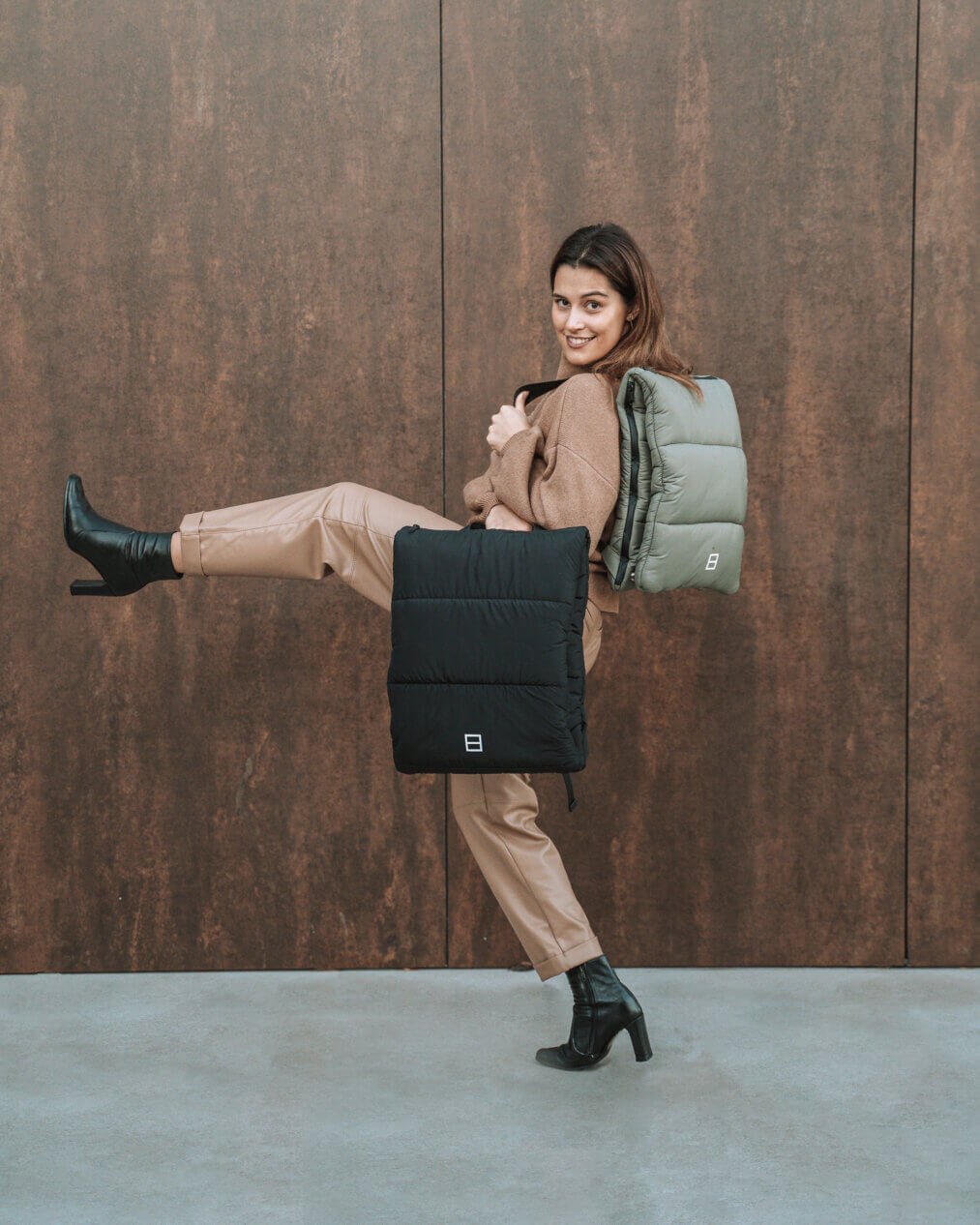 Joana em frente a uma parede a mostrar as mochilas By The Book