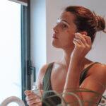 Joana a ver-se no espelho e a colocar o óleo no rosto