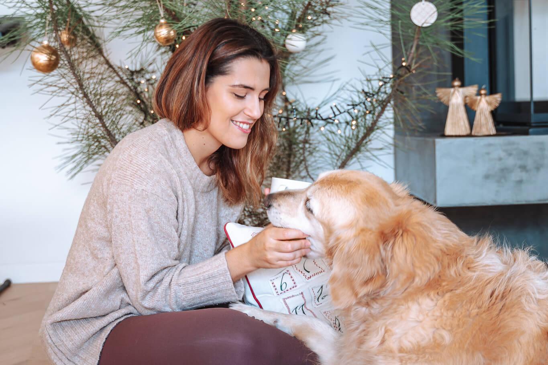 Joana e a cadela Noa sentadas em frente ao pinheiro de Natal