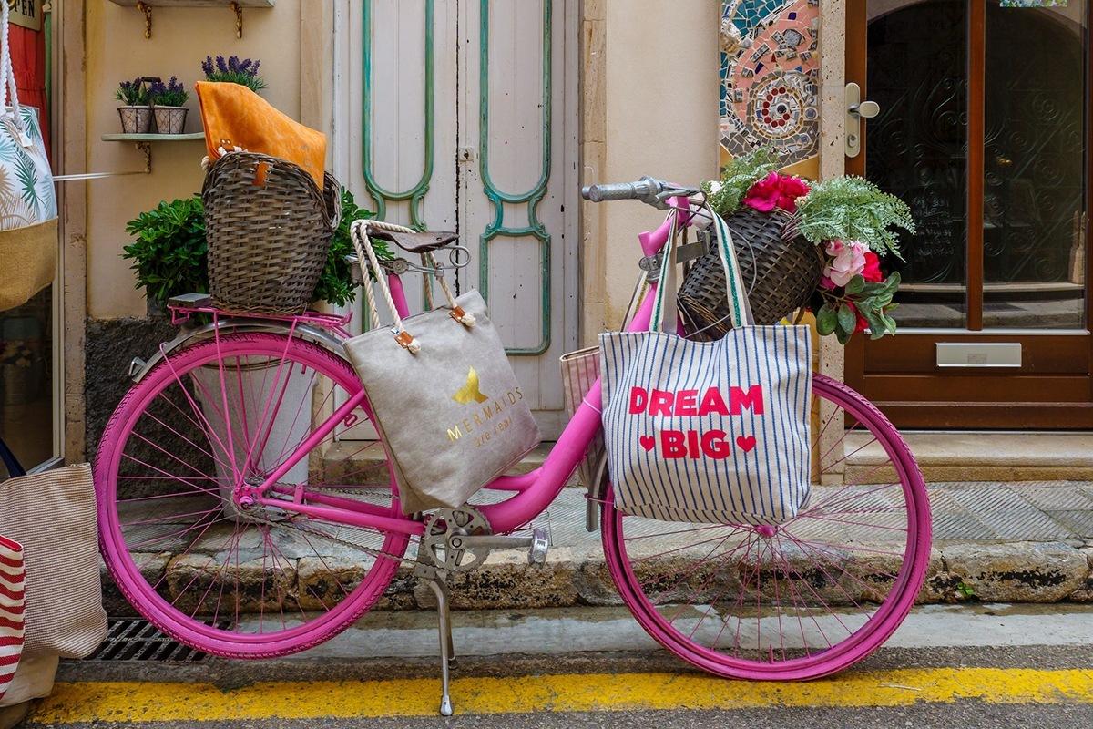 Bicicleta rosa com um saco pendurado a dizer Dream Big