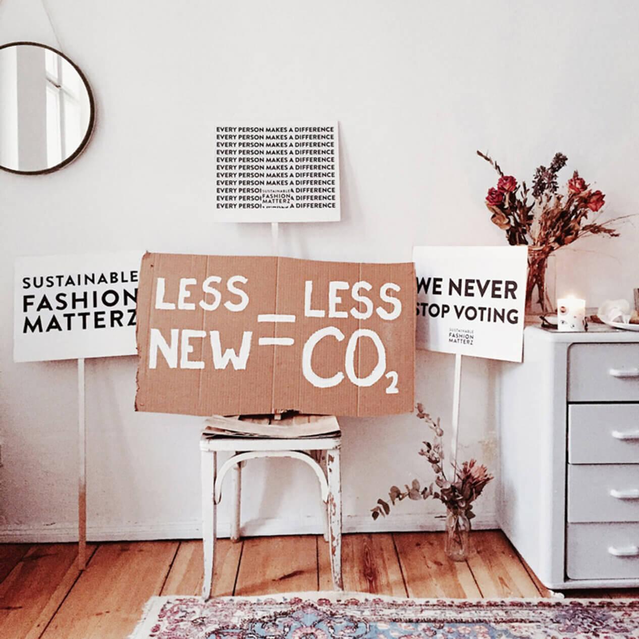 """Cartaz em cima de uma cadeira com frase """"Less New = Less CO2"""""""