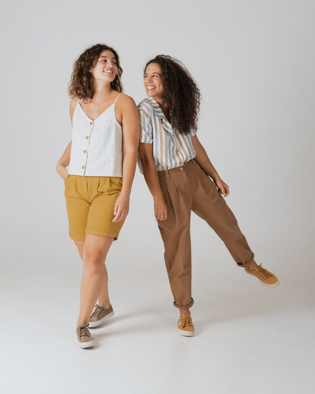 Duas raparigas animadas lado a lado sob fundo branco