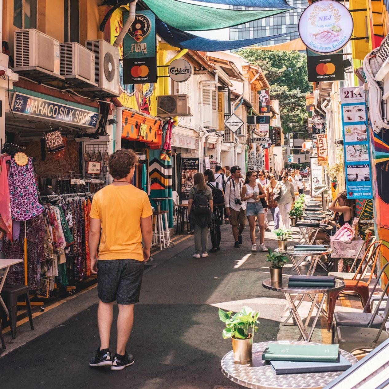 Rua com lojas locais em ambos os lados e várias pessoas a passar nela